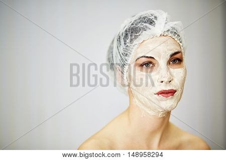 Portrait of woman with cosmetic mask on face and mesh hair cap on head.