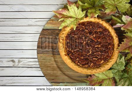 Whole pecan pie in fall maple leaves on wood plate