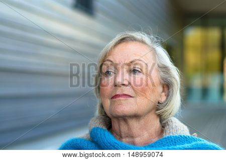 Thoughtful elderly lady with a serious speculative expression looking off to the side watching something with her head tilted back
