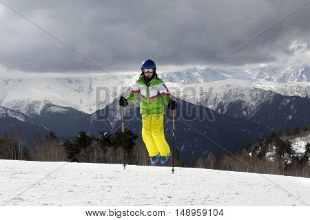 Young Skier Jump With Ski Poles In Sun Mountains And Cloudy Gray Sky