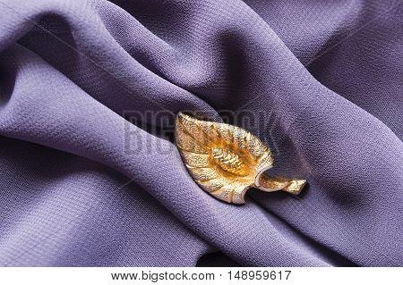 Golden leaf shaped brooch on purple draped silk