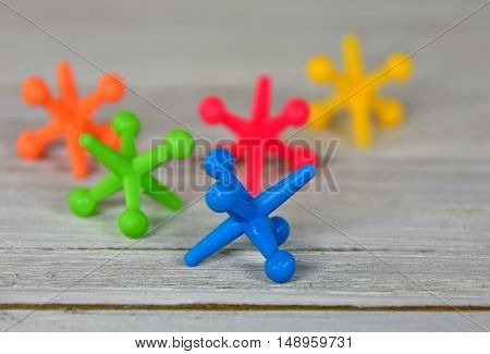close up of colorful toy jacks on rustic wood