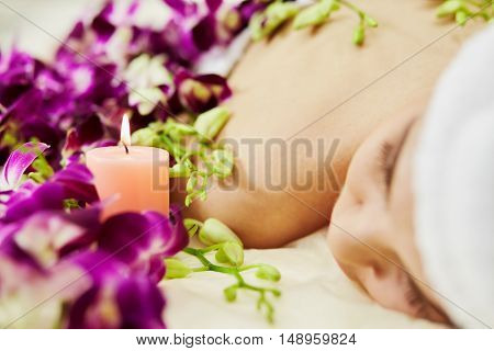 Woman lies on couch near flowers and burning candle in beauty salon, focus on candle.
