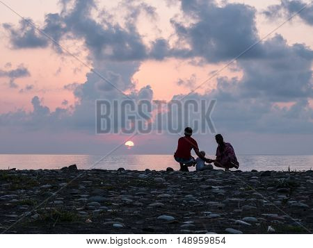 Happy family - father, mother, baby son see sunset sea surf on black sand beach. Active parents and people outdoor activity on tropical summer vacations with children.
