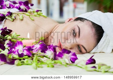 Face of woman that lies on couch among flowers and burning candle in beauty salon.