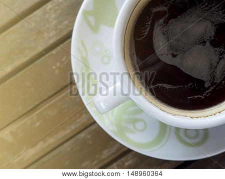 Hot cup of black coffee on wood table with sunlight (Color filter effect)