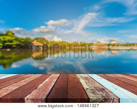 Wood pier or walkway or an old wooden table with blur image of lake and beautiful blue sky in background.