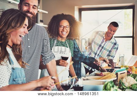 Group of diverse friends drinking and cooking in front of long food preparation table indoors