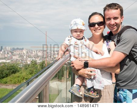 Happy family with a beautiful baby looking at the city from a great height of the mountains.