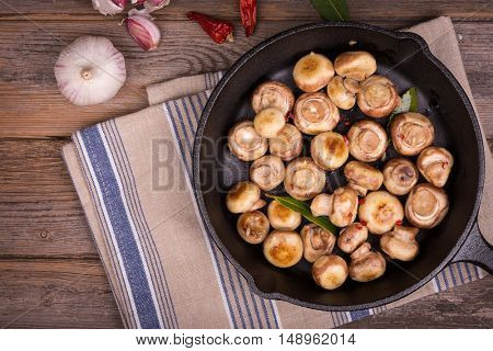 Button mushrooms with garlic and herbs, fried in a cast iron skillet, resting on a tea towel over an old wood background.