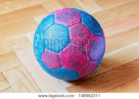 Dirty blue and red handball ball on a wooden parquet floor