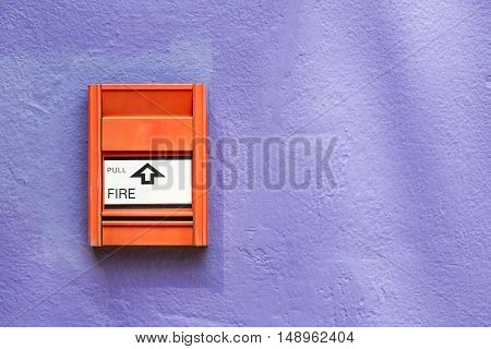 Fire alarm switch on violet painted wall