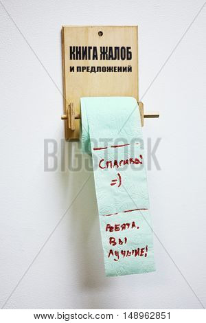 Wooden holder for toilet paper with inscription Customer Feedback Book and roll with text Thanks Guys You Are The Best.