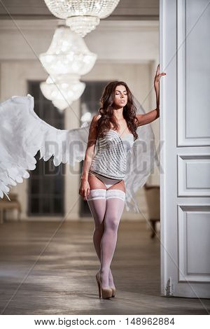 Young woman with her eyes close in white underwear, stockings and angel wings behind her back in room leaning her hand on door.