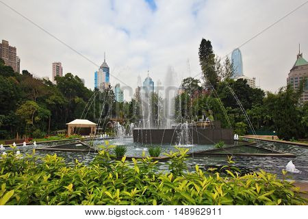 HONG KONG, DECEMBER 11, 2014: Hong Kong Special Administrative Region. The modern city. Elegant square with fountain, surrounded by flower beds