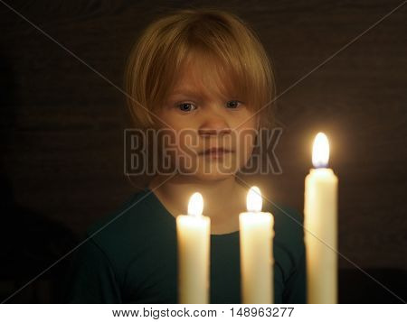 Little girl looks at three large candles
