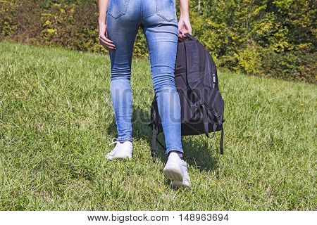 Young girl with a backpack hiking in nature at green grass