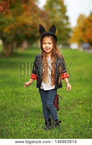 happy little child posing for the camera baby girl laughing and playing in the autumn on the nature walk outdoors