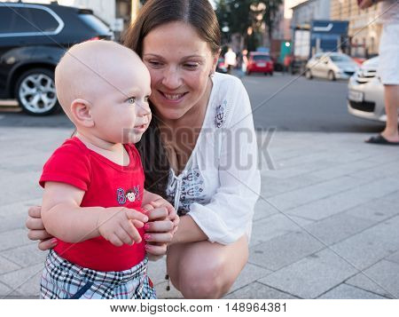 Young mother with her toddler son playing outdoors in city.