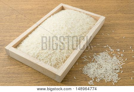 Cuisine and Food Uncooked White Long Rice Basmati Rice or Thai Jasmine Rice in A Wooden Tray.