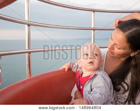 Young mother with her toddler son playing outdoors on Ferris wheel.