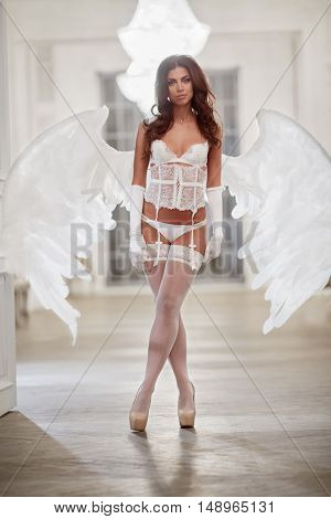 Young woman in white underwear, stockings and angel wings behind her back in room against doorway.