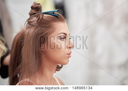 Head in profile of young woman while visagist makes hairdo.