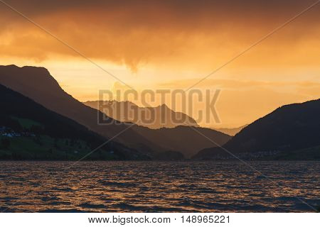 Beautiful view of the lake Resia. Dramatic sky and colorful sunset. Alps, Italy, Europe.