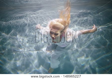 Young blond woman in white dress swims with her eyes close in swimming pool underwater.