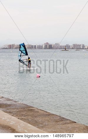 Girl Windsurfing Near The Coast Of Rosas In Spain