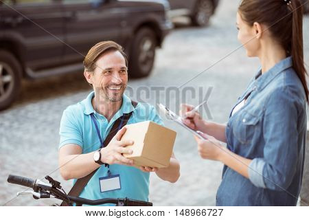 Work for your comfort. Positive content professional courier holding the parcel and delivering it while nice client signing the paper