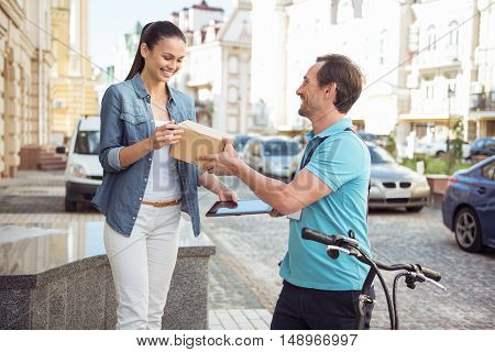 Work with pleasure. Positive smiling professional courier delivering the parcel and giving to delighted client who is standing on the porch