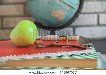 World teachers ' Day in school. Still life with books, globe, Apple glasses.