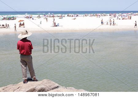 a man observes a beach with several people