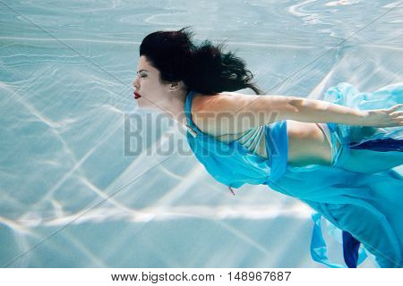 Young black-haired woman in blue dress swims underwater with her eyes close.