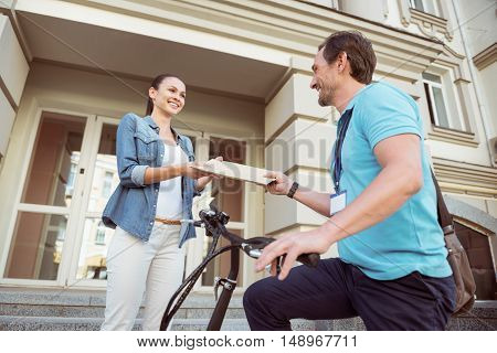 Pleasant anticipation. Cheerful beautiful woman standing on the porch while professional positive courier delivering post for her