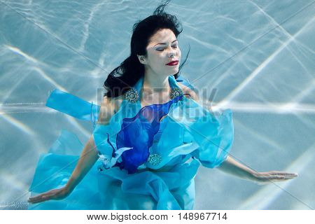 Young black-haired smiling woman in blue dress poses with her eyes close underwater.