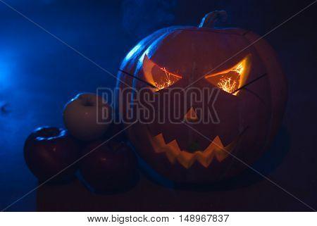 Autumn arrangement of pumpkins and apples, a pumpkin-lantern on a wooden table, happy Halloween