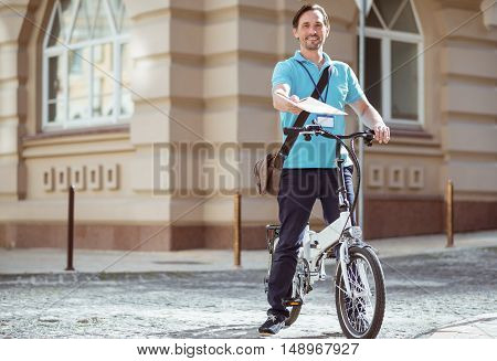 Here you are. Cheerful delighted professional courier riding a bicycle and delivering post while expressing positivity