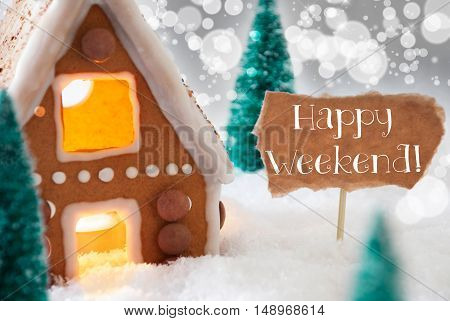 Gingerbread House In Snowy Scenery As Christmas Decoration. Christmas Trees And Candlelight For Romantic Atmosphere. Silver Background With Bokeh Effect. English Text Happy Weekend