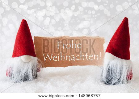 Christmas Greeting Card With Two Red Gnomes. Sparkling Bokeh Background With Snow. German Text Frohe Weihnachten Means Merry Christmas