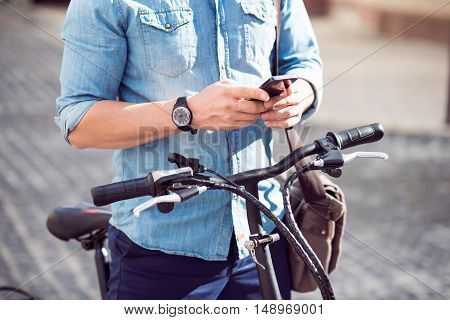 Everyday life. Close up of cell phone in hands of pleasant man holding a cellphone and standing with the bicycle in the street