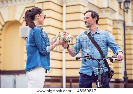Bright day. Positive delighted adult man presenting flowers to his girlfriend while standing in the street with bicycle
