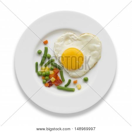 Fried egg in a shape of the heart and some vegetables on a white plate. Top view.