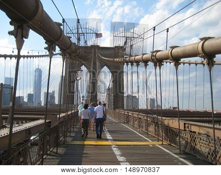 People walking on pedestrian path across famous Brooklyn Bridge in New York City, USA during beautiful sunny day Structural details and cables close up