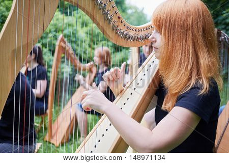 Musicians play harps outdoors in park.