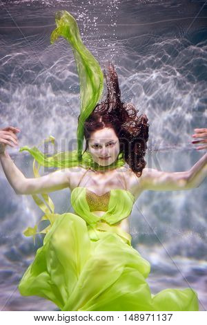 Young woman in yellow-green dress poses in swimming pool underwater.
