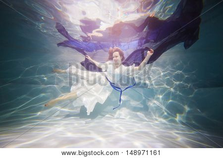 Smiling young woman in white dress poses in swimming pool with dark-blue fabric in hands underwater.