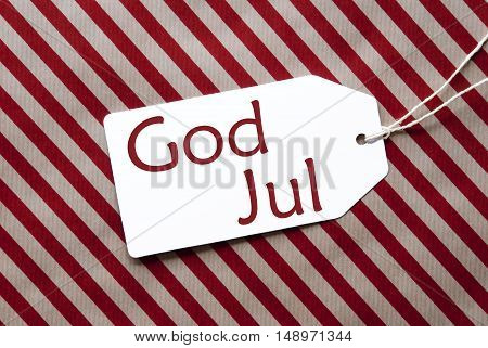 One Label On A Red And Brown Striped Wrapping Paper. Textured Background. Tag With Ribbon. Swedish Text God Jul Means Merry Christmas