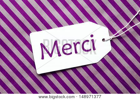 One Label On A Purple Striped Wrapping Paper. Textured Background. Tag With Ribbon. French Text Merci Means Thank You